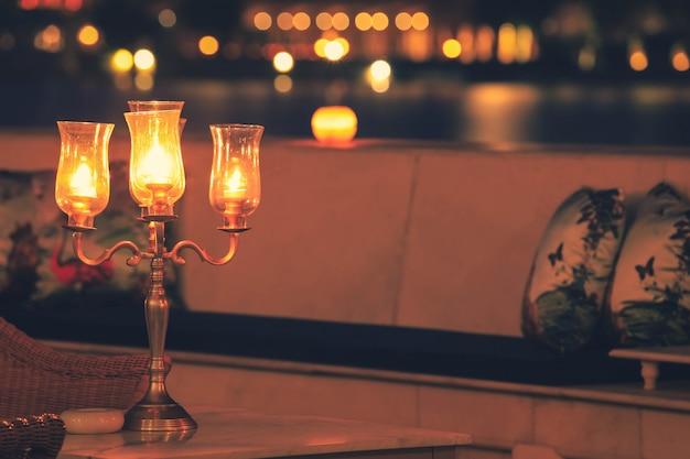 Romantisches abendessen bei kerzenlicht auf tisch mit bokeh-hintergrund, romantisches abendessenkonzept.