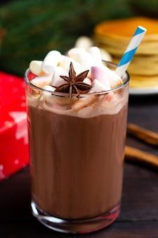 Romantisches abendessen. ein glas heiße schokolade und ein rotes geschenk auf dem hintergrund.