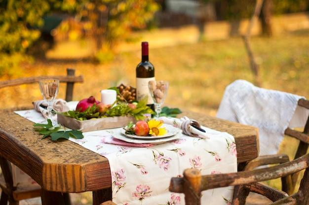Romantisches abendessen im herbstgarten, gedeckter tisch für ein schönes abendessen. wein, obst, granatapfel und blumen. picknick im freien.