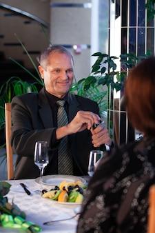 Romantisches abendessen im restaurant, ein mann öffnet champagner und lächelt, irgendwie hinter der schulter einer frau.