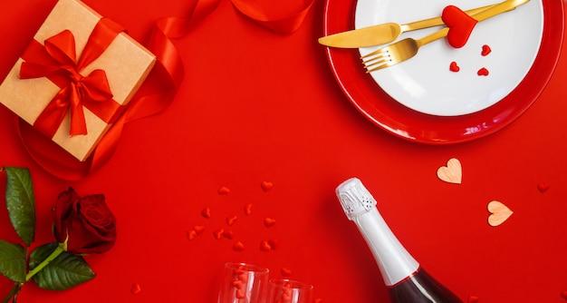 Romantisches abendessen zum valentinstag auf rotem grund.
