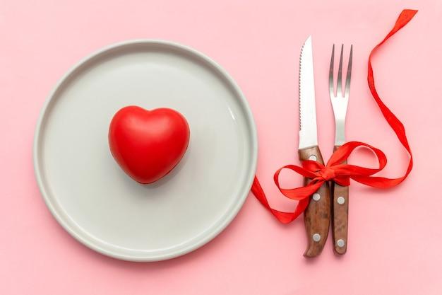 Romantisches abendessen zum valentinstag, datierung, liebeskonzept. tabble servieren mit besteck und herzdekor auf rosa hintergrund.