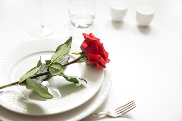 Romantisches abendessen zum valentinstag oder geburtstag. romantisches gedeck mit rotrose.