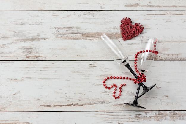 Romantisches abendessen zum valentinstag - rotes herz, gläser mit perlenkette.
