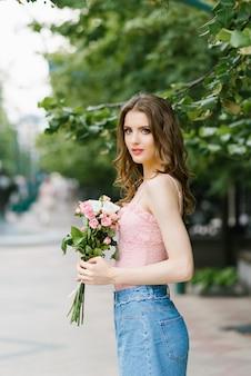 Romantisches bild eines jungen mädchens, das auf eine sommerstraße im park mit einem blumenstrauß von rosen, von stadterholung und von weg geht. porträt