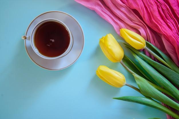 Romantisches bild mit gelben tulpen und teeschale auf blauem hintergrund