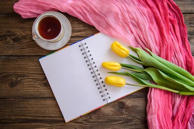 Romantisches bild mit notizblock, tulpen und einer tasse tee auf hölzernem hintergrund