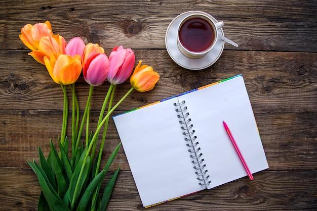 Romantisches bild mit tulpen, tee, notizbuch, draufsicht