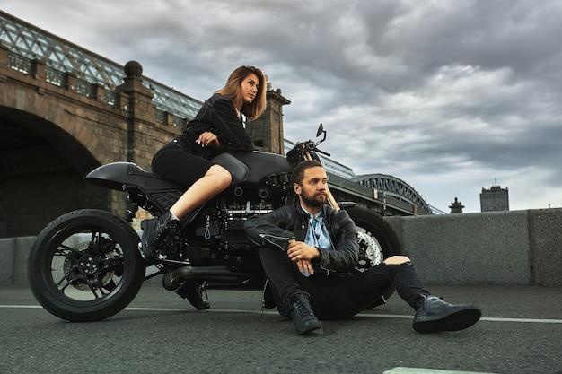 Romantisches date auf dem motorrad junge frau sitzt auf einem motorrad und schaut den mann an, der auf dem boden sitzt paar verliebt in sonnenuntergang unter der brücke in der stadt.