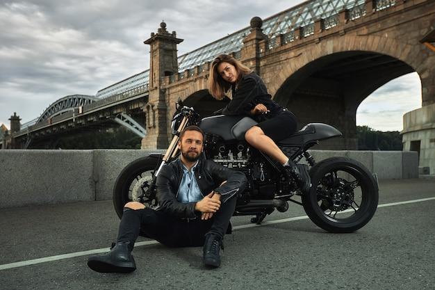 Romantisches date auf dem motorrad. junge frau sitzt auf einem motorrad und sieht den mann an, der auf dem boden sitzt. paar verliebt in sonnenuntergang unter der brücke in der stadt.