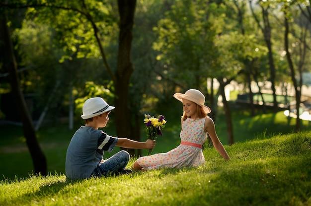 Romantisches date für kinder im sommerpark, freundschaft, erste liebe. junge gibt einem mädchen blumenstrauß. kinder haben spaß im freien, glückliche kindheit