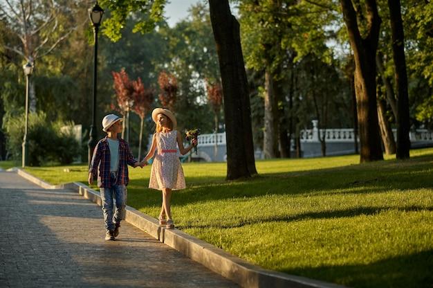 Romantisches date für kinder im sommerpark, freundschaft, erste liebe. junge und mädchen mit blumenstrauß auf gehweg. kinder haben spaß im freien, glückliche kindheit