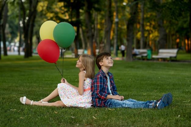 Romantisches date für kinder im sommerpark, freundschaft, erste liebe. junge und mädchen mit luftballons, die rücken an rücken auf einem gras sitzen. kinder haben spaß im freien, glückliche kindheit