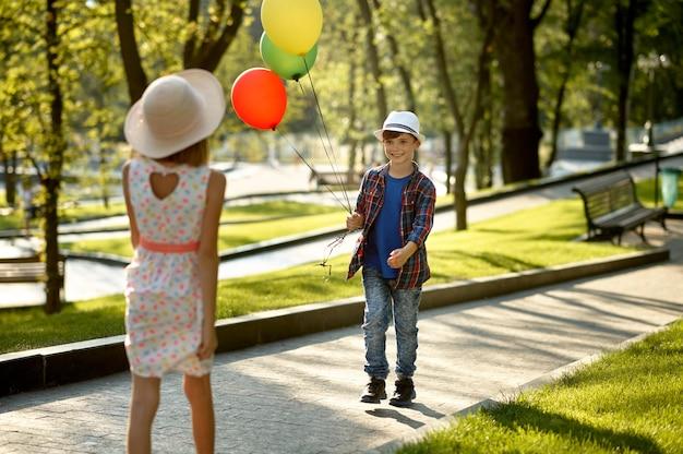 Romantisches date für kinder im sommerpark, freundschaft, erste liebe. jungen und mädchen, die mit luftballons gehen. kinder haben spaß im freien, kindheit