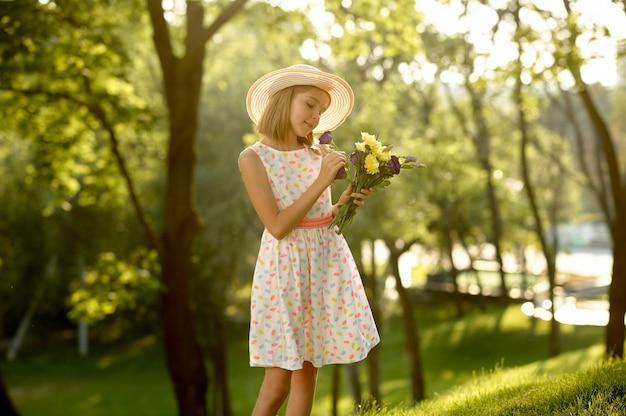 Romantisches date für kinder im sommerpark, freundschaft, erste liebe. kleines mädchen mit blumenstrauß. kinder haben spaß im freien, glückliche kindheit