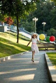 Romantisches date für kinder im sommerpark, freundschaft, erste liebe. kleines mädchen mit luftballons. kind hat spaß im freien, glückliche kindheit