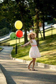 Romantisches date für kinder im sommerpark, freundschaft, erste liebe. kleines mädchen mit luftballons. kinder haben spaß im freien, glückliche kindheit