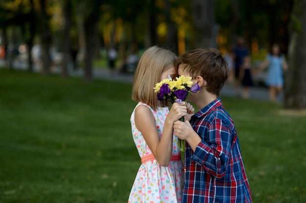 Romantisches date für kinder im sommerpark, freundschaft, erster liebeskuss. junge und mädchen mit blumenstrauß auf gehweg. kinder haben spaß im freien, glückliche kindheit