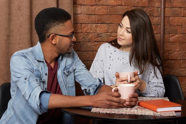 Romantisches entspanntes paar sitzt im café am tisch, schaut sich an, hält tassen kaffee oder tee in den händen und ist unterschiedlicher rasse