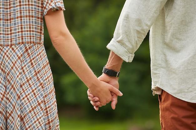 Romantisches erwachsenes paar, das hände in der rustikalen landschaftslandschaft hält