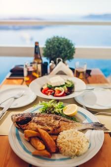 Romantisches flitterwochenabendessen für zwei auf santorini-insel, griechenland mit küste, vulkanansicht. griechischer salat und meeresfrüchte