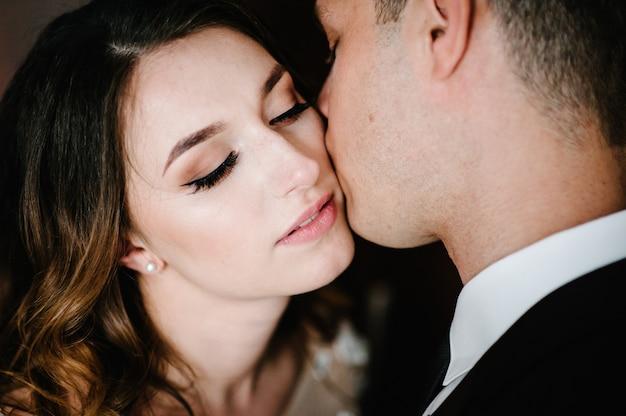Romantisches foto. mann umarmt liebevoll eine zarte frau. junges paar verliebt am valentinstag. nahansicht.