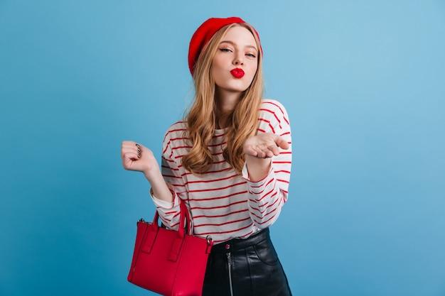 Romantisches französisches mädchen. stilvolle frau in der baskenmütze, die rote handtasche hält.
