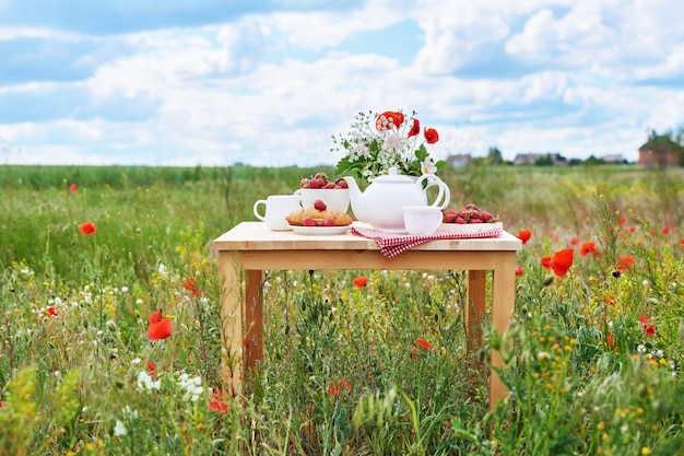 Romantisches französisches oder ländliches valentinstagfrühstück: tee, erdbeeren, croissants auf dem tisch im mohnfeld. land und gemütlich guten morgen wochenende konzept.