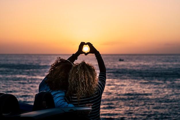 Romantisches freundschaftskonzept mit zwei lockigen damen, die von hinten betrachtet werden, die herdliebeszeichen mit händen tun, um die sommerferienferienreise vor der schönheit des naturozeans zu feiern