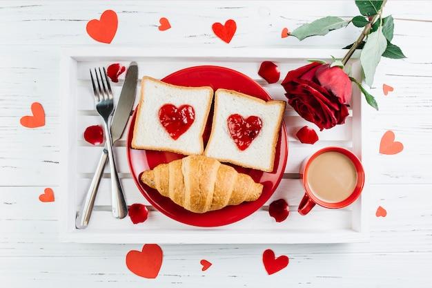 Romantisches frühstück auf hellem holztablett