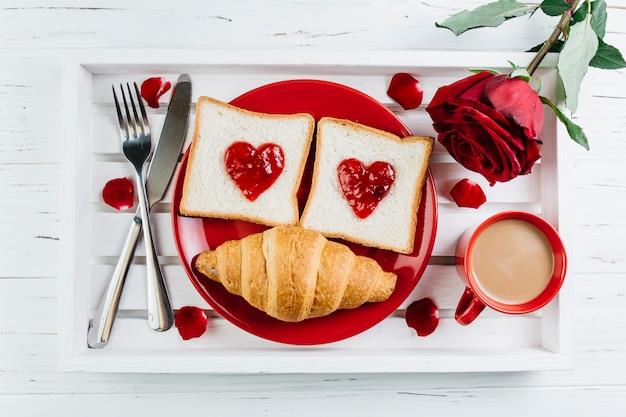 Romantisches frühstück auf weißem hölzernem behälter