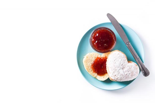 Romantisches frühstück, herzförmiges brötchen und beerenmarmelade auf weißer oberfläche