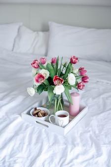 Romantisches frühstück im bett. blumenstrauß. rosen und tulpen.