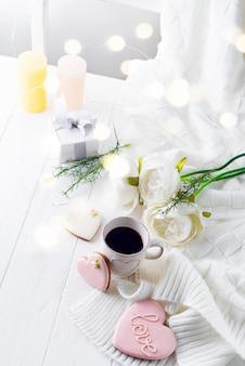 Romantisches frühstück im bett. kaffee, kekse, geschenkbox und blume auf holztisch. valentinstag-konzept