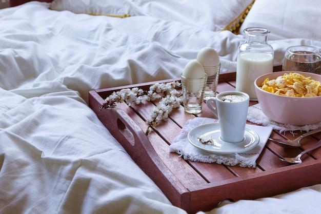 Romantisches frühstück im bett mit frühlingsblumen. fensterlicht