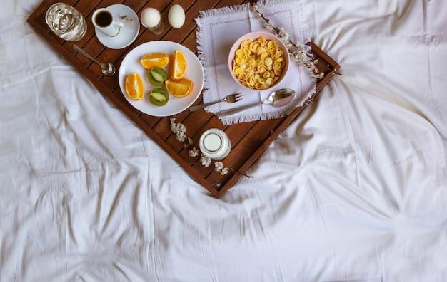 Romantisches frühstück im bett mit frühlingsblumen. flache lage, kopierraum