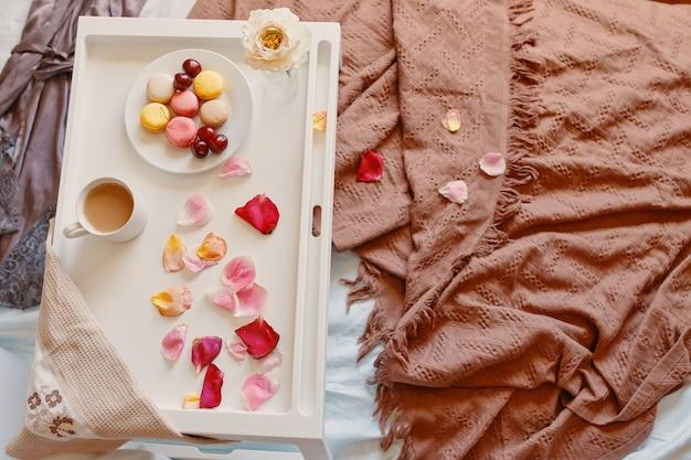 Romantisches frühstück im bett mit untertasse mit rosenblättern, makronen und kirschen