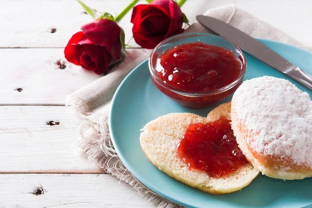 Romantisches frühstück mit herzförmigem brötchen, beerenmarmelade und rosen auf weißem holztisch