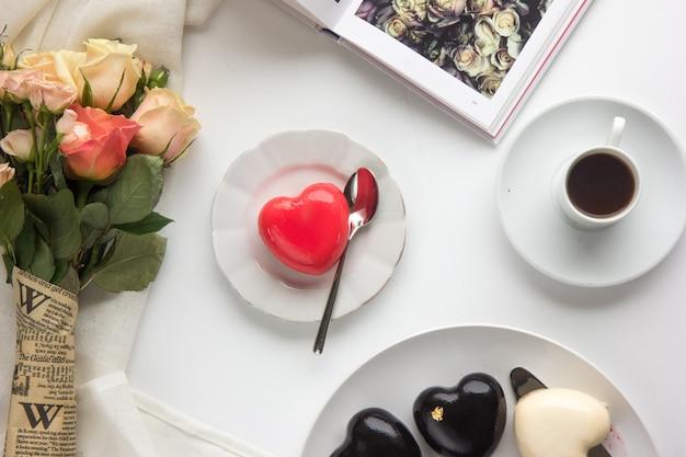 Romantisches frühstück mit herzförmigen kuchen und kaffeetasse