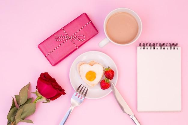 Romantisches frühstück mit rose und geschenk serviert