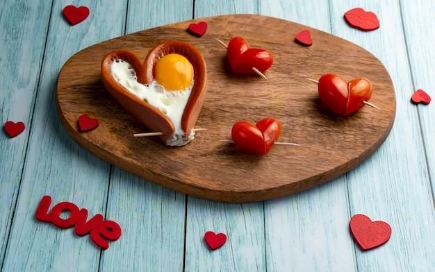 Romantisches frühstück mit würstchen in form eines herzens. tomatenherzen. horizontale ausrichtung
