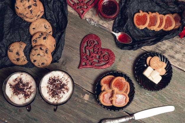 Romantisches frühstück. zwei tasse kaffees, cappuccino mit schokoladenplätzchen und kekse nähern sich roten herzen auf holztischhintergrund. valentinstag. liebe. ansicht von oben.
