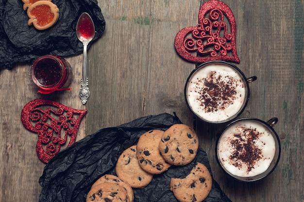 Romantisches frühstück. zwei tassen kaffee, cappuccino mit schokoladenplätzchen und keksen nahe roten herzen auf hölzernem tischhintergrund. valentinstag. liebe. draufsicht.