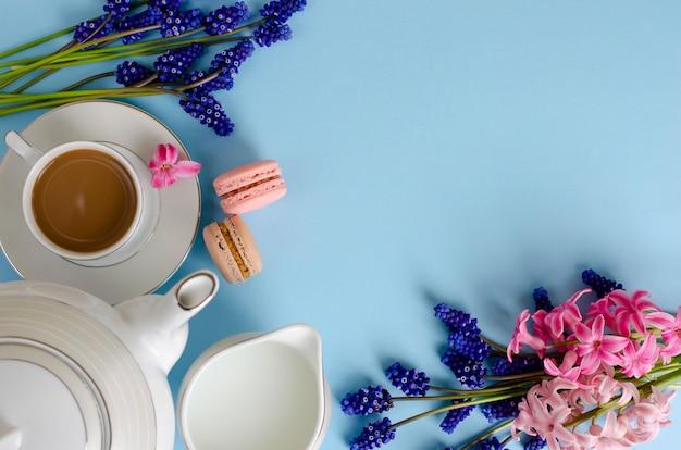 Romantisches frühstückskonzept. tasse kaffee mit milch, makronen, milchglas auf pastellblau