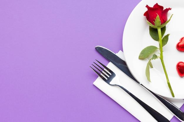 Romantisches gedeck der draufsicht auf purpurrotem hintergrund