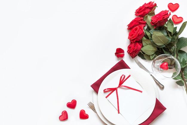 Romantisches gedeck mit blumenstrauß von roten rosen. von oben betrachten. valentinstag.