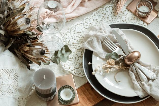 Romantisches gedeck mit brennenden kerzen und getrockneten blumen für die hochzeit mit vielen dekorativen details.