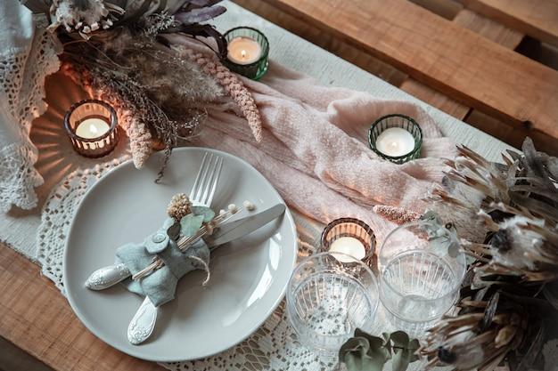 Romantisches gedeck mit brennenden kerzen und getrockneten blumen für eine hochzeit oder valentinstag