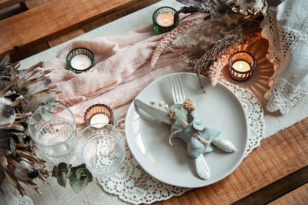Romantisches gedeck mit brennenden kerzen und getrockneten blumen für eine hochzeit oder valentinstag.