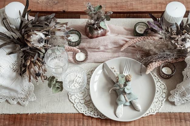 Romantisches gedeck mit kerzen und getrockneten blumen für eine hochzeit oder valentinstag